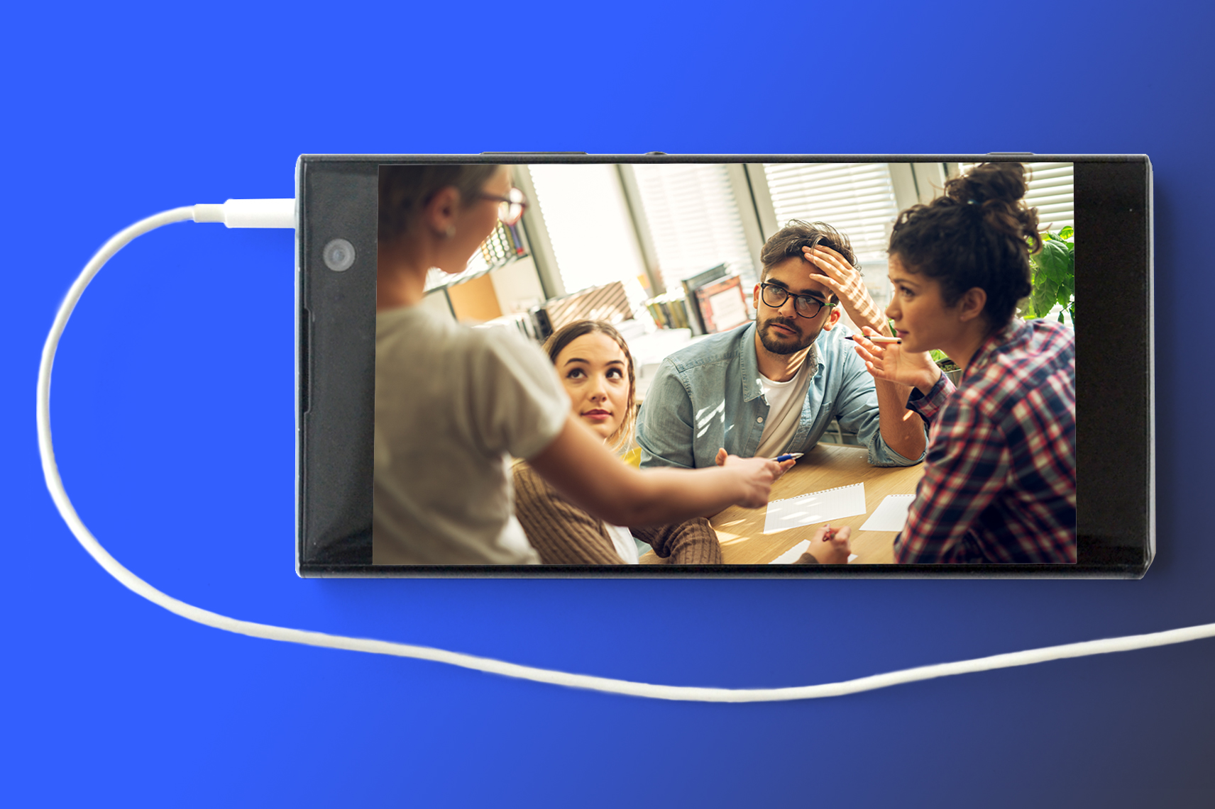 Image of cell phone with earbud cord attached. An image of 4 individuals around a table appears on the phone.